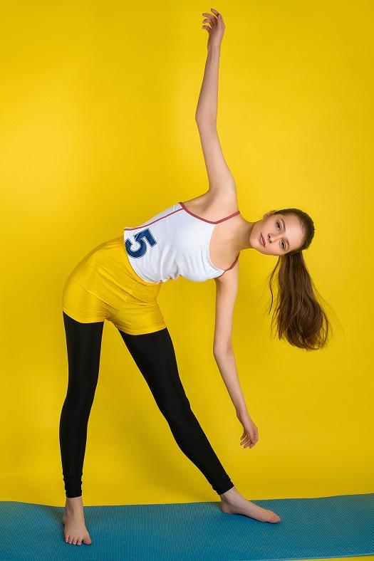 Tekst przedstawia łodą dziewczynę , która wykonuje zgięcie i rotację tułowia. U dziewczyny tej konieczne jest badanie aktywne wykonane przez specjalistę takiego jak ortopeda katowice.